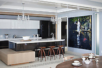 The bar stools at the kitchen counter are by Andrew Dominic. The Messenger by Matthew Hindley presides over the kitchen, designed and fitted by Assirelli Italian Design. The imported Reichenbach tea set takes centre stage on the table.