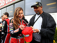 Feb 9, 2014; Pomona, CA, USA; NHRA top fuel dragster driver Leah Pritchett sign an autograph for a fan during the Winternationals at Auto Club Raceway at Pomona. Mandatory Credit: Mark J. Rebilas-
