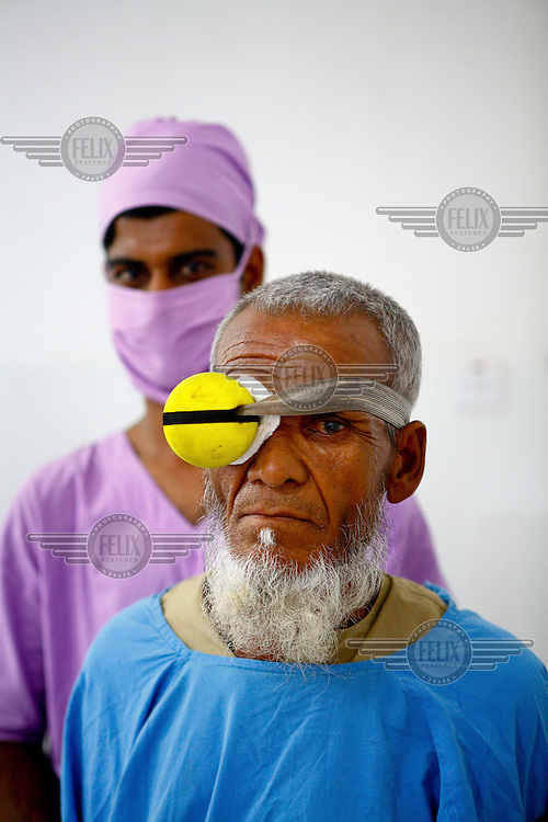An elderly man, wearing an eye protector following a procedure, and a member of the surgical staff together at the Islamia Eye Hospital. Founded in 1960, about 20,000 eye surgeries are performed in the main hospital annually, that is approximately 10% of the total cataract surgeries in the country.
