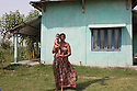 Nepal - Meghauli (Therai region) - A woman stands in front of her house holding her baby. Most of the workers come from the Therai region of Nepal where very few working age male are left and where women end up living alone for years having to take care of the children, the land and do all sorts of jobs they were not used to do before. According to UN figures, 7,2 million Nepalis work abroad (4 millions of them in India). Half of them are undocumented, 1700 migrant workers leave Nepal every day, 2/3 dead bodies arrive at Kathmandu airport every day. According to the World Bank, in 2013 Nepal received more than 5 billion USD in remittances from abroad. This constitutes 24.7 percent of the GDP, the third highest percentage in the world after Tajikistan and Kyrgyzstan. A third of all Nepali households, and 35% of rural households, have at least one member working and living abroad. 24.8 percent of Nepalis still live under the poverty line. Nepali GDP per capita (PPP) stands at 1,102 USD, the twentieth lowest in the world. Since 1971, Nepal has been classified as one of the 48 least developed countries by the UN.