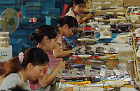 Female workers on the busy production line at one of the worlds most successful brush manufacturers in the world. The Yixing Zhenxin Made Brush Co. Ltd produces a staggering 220,000 brushes every day using relatively non-high-tech but labour intensive methods for a variety of domestic and international clients. International clients include the home Depot, Wallmart and ICI to name a few..