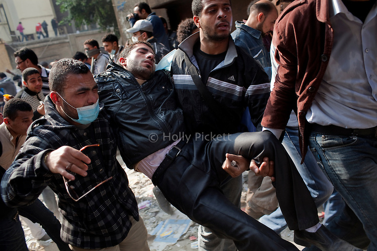 Demonstrators carry a man who passed out from inhaling tear gas on Mohamed Mahmoud Street to a nearby field hospital Tahrir Square in Cairo, Egypt, Tuesday, November 22, 2011. Clashes between Central Security Forces and demonstrators demanding an end to military rule continued into a fourth day.