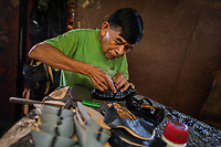 A Salvadoran shoemaker works on a new patent leather shoe, attaching a bowknot, in a shoe making workshop in San Salvador, El Salvador, 16 November 2016.
