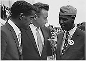 """Sammy Davis, Jr., actor and performer, left, and Roy Wilkins, Executive Secretary of the National Association for the Advancement of Colored People, right, are interviewed by an unidentified reporter, center,  at 1963 March on Washington for Jobs and Freedom the Washington, D.C. , August 28, 1963.  This is the march where Dr. Martin Luther King, Jr. gave his """"I have a Dream"""" speech.<br /> Credit: National Archives via CNP"""