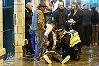 Pictured: Police and bystanders see to a man that collapsed on the ground in Wind Street, Swansea, south Wales, UK. Friday 21 December 2018<br /> Re: Black Eye Friday, also known as Mad Friday or Black Friday which is the last Friday before Christmas Day.