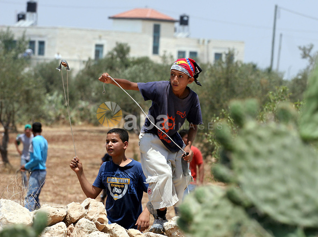 Palestinian boys hurl stones at Israeli border police officers during a demonstration against the construction of the controversial Israeli cement barrier in the West Bank village of Nilin near Ramallah. Sixteen Palestinians and one Israeli were lightly wounded today when Israeli security forces dispersed a protest against the West Bank separation barrier, Palestinian medics said.