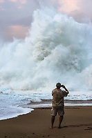 At twilight, a massive wave explodes onto the shore at Lumahai Beach on Kaua'i as a man takes a photo in the foreground.