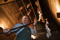 Europe/France/Rhone-Alpes/74/Haute-Savoie/ Chamonix:  Pierre Carrier acroche ses charcuteries de montagne dans la cheminée- fumoir  (Borne en Chamoniard) du Restaurant: La Maison Carrier [Non destiné à un usage publicitaire - Not intended for an advertising use]