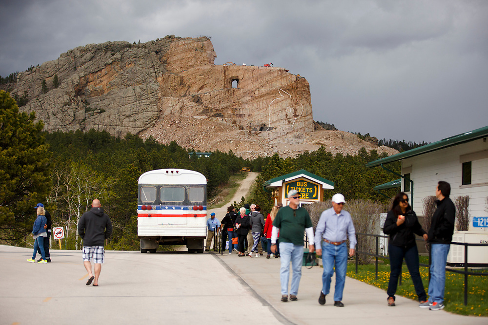 Tourists disembark a bus after a tour of the Crazy Horse Memorial in South Dakota on Sunday, May 21, 2017. (Photo by James Brosher)
