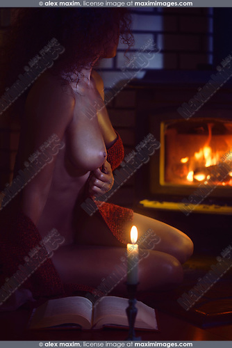 Artistic erotic photograph of a beautiful sexy naked woman sitting by the fireplace looking at the fire taking off a cozy warm red sweater revealing her nude body shining in dim candle light