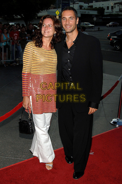 """CHIARA GIORDANO & RAOUL BOVA.The  Los Angeles Premiere of """"The Brothers Grimm"""" held at The DGA Theatre, Los Angeles, CA..August 8th, 2005.Photo credit: Jacqui Wong/AdMedia.full length married husband wife black suit white trousers orange yellow striped top.www.capitalpictures.com.sales@capitalpictures.com.© Capital Pictures."""