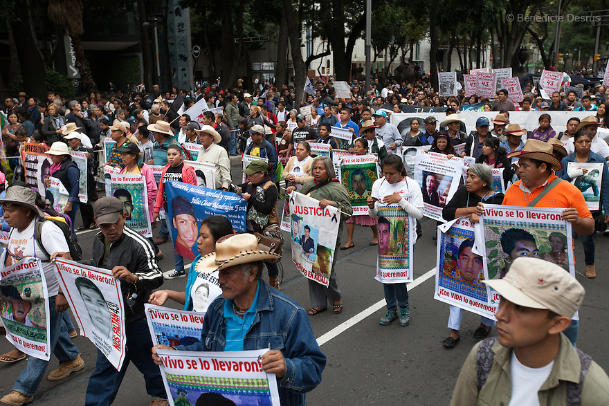 Parents and Relatives of some of the 43 missing students from Mexico's Ayotzinapa College Raul Isidro Burgos hold posters of them during a march to mark the one-year anniversary of their disappearance, in Mexico City, Mexico on September 26, 2015. Families of the missing and international experts cast doubt on Mexican government's official account of the incident: that municipal police handed the students over to a local drug gang who burned their bodies in a nearby garbage dump. The families asked the government to launch a new internationally supervised investigation and to review Mexico's own investigators. More than 25,000 people have disappeared in Mexico since 2007, according to the government. (Photo by BénédicteDesrus)