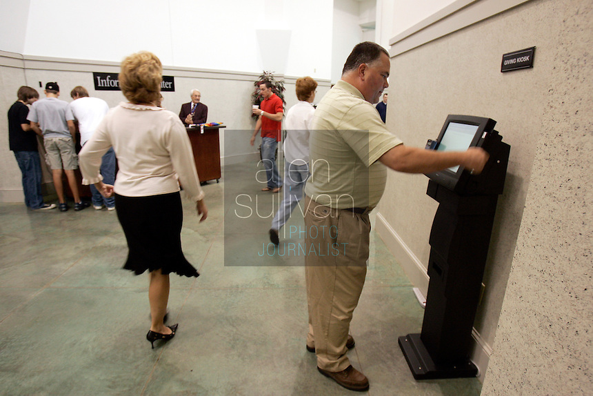 Todd Lewer, of Evans, Ga., tries unsuccessfully to use one of three kiosks at Stevens Creek Church to make a donation. Pastor Marty Baker installed the kiosks in 2005 to enable people who carry little cash to donate with credit cards or check cards. So far, Baker said, up to 25 percent of donations to the church come through the kiosks and he expects about $200,000 from them this year.<br />