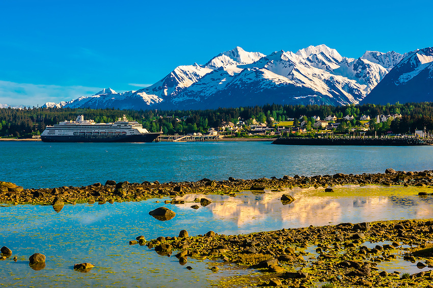 "Holland America Line's cruise ship ""Zaandam"" in port at Haines, Alaska USA. Haines is surrounded by mountains and water. Rising high above the town are the Takinsha Mountains and Chilkat Range to the south, Takshanuk Mountains to the north and Coast Mountains to the east across the Lynn Canal."