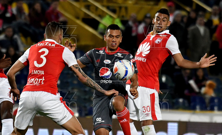 BOGOTA - COLOMBIA - 21 - 03 - 2018: Jose Moya (Izq.) y Yeison Gordillo (Der.) jugadores de Independiente Santa Fe, disputan el balón con Carlos Lizarazo (Cent.) jugador jugador de America de Cali, durante partido aplazado de la fecha 3 entre Independiente Santa Fe y America de Cali, por la Liga Aguila I 2018, en el estadio Nemesio Camacho El Campin de la ciudad de Bogota. / Jose Moya (L) and Yeison Gordillo (R) player of Independiente Santa Fe struggle for the ball with Carlos Lizarazo (C) player of America de Cali, during a posponed match of the 3rd date between Independiente Santa Fe and America de Cali, for the Liga Aguila I 2018 at the Nemesio Camacho El Campin Stadium in Bogota city, Photo: VizzorImage / Luis Ramirez / Staff.