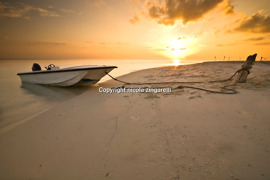 Maldive Islands, Indian Ocean. Dinghy sitting on the beach while the mother vessel is moored inside a laggon at sunset with calm water and beautiful colors