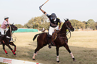 A Royal Jaipur Polo Team player tries to hook the mallet of a Western Australia Polo Team player during the Royal Jaipur Polo Team (in pink) vs Western Australia Polo Team (in black) Argyle Pink Diamond Cup, organised as part of the 2013 Oz Fest in the Rajasthan Polo Club grounds in Jaipur, Rajasthan, India on 10th January 2013. Photo by Suzanne Lee
