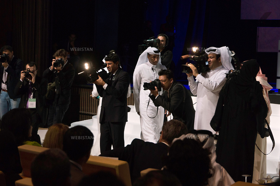 Qatar, Doha, Qatar National Convention Centre <br /> Opening night of the World Innovation Submit for Education 2012 (WISE): some journalists photograph Sheikha Mozah bint Nasser Al Missned, second of the three wives of Sheikh Hamad bin Khalifa Al Thani, former Emir of the State of Qatar, from 1995 to 2013 and mother of the current emir, Sheikh Tamim bin Hamad Al Thani. <br /> Founder of the Qatar foundation for education founded in 1996, she presides at the Foundation's annual convention every year. Named UNESCO Special Envoy for Basic &amp; Higher Education in 2013, she oversees all Qatari reforms related to education and the Family Law adopted in 2006 in Qatar. <br /> Qatar is one of the Arab peninsular emirates, on the Persian Gulf shoreline. Bordered by Saudi Arabia, Qatar's economy relies on oil and gas. Being the world's fourth-largest gas exporter, gas remains the major driver of Qatar's economy. The emirate is governed by Sheikh Tamim bin Hamad Al Thani who became at the age of 33 Emir of Qatar on 25 June 25th, 2013 after his father's abdication. He is the youngest emir at the head of an Arab State.<br /> On June 5th, 2017, Saudi Arabia, the United Arab Emirates, Egypt, Bahrain, Yemen, Libya, Mauritania, the Maldives, and Mauritius broke off diplomatic relations with Qatar, accusing the emirate of supporting several terrorist groups. As its Gulf neighbours enforced the closure of all land, air and sea borders to Qatar, the country is quarantined.<br /> <br /> 