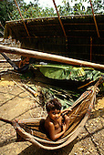 Roraima, Brazil. Yanomami Indian child in a traditionally made vegetable fibre hammock which is lined with a blanket.