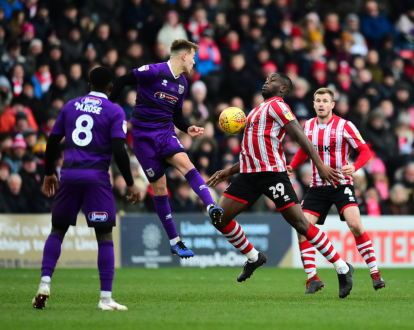 Grimsby Town's Jake Hessenthaler clears under pressure from Lincoln City's John Akinde<br /> <br /> Photographer Andrew Vaughan/CameraSport<br /> <br /> The EFL Sky Bet League Two - Lincoln City v Grimsby Town - Saturday 19 January 2019 - Sincil Bank - Lincoln<br /> <br /> World Copyright © 2019 CameraSport. All rights reserved. 43 Linden Ave. Countesthorpe. Leicester. England. LE8 5PG - Tel: +44 (0) 116 277 4147 - admin@camerasport.com - www.camerasport.com