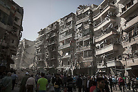 Destroyed buildings are seen along one street where Syrian residents look for bodies after an aistrike hits a residential area in Al-Ansari, a neighborhood under control of the rebel fighters in Aleppo, Syria.