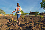 Rato Paul, 13, plants corn in the Rhino Refugee Camp in northern Uganda. As of April 2017, the camp held almost 87,000 refugees from South Sudan, and more people were arriving daily. About 1.8 million people have fled South Sudan since civil war broke out there at the end of 2013. About 900,000 have sought refuge in Uganda. <br /> <br /> The boy's family fled from Yei, South Sudan, in 2016.