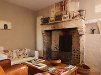 The original fireplace in the living has been restored and family photographs are displayed on its mantelpiece