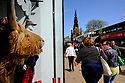 Edinburgh, UK. 15.04.2017. Women walk past a highland cow's head in a shop window, on Princes Street. Photograph © Jane Hobson.