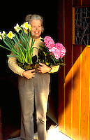 Woman age 66 holding flowers for Easter Service.  Western Springs  Illinois USA