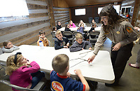 NWA Democrat-Gazette/ANDY SHUPE<br /> Laura Jennings (right), park interpreter at Battlefield State Park in Prairie Grove, smiles as she shows children a batch of biscuits made in a Dutch oven Friday, March 23, 2018, during a Pioneer craft day camp at the park. Campers learned about weaving, sewing, native plants, and other skills used by early settlers.
