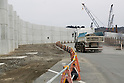 A construction truck runs next to a 1.61 km long tsunami barrier in Kesennuma city on February 9, 2016, Miyagi Prefecture, Japan.  5 years after the 2011 Tohoku earthquake and tsunami the rebuilding project still goes on in Kesennuma. The controversial sea wall is designed to protect the fishing town that lost over 1000 lives in the disaster, although many locals complain that it is an eyesore and an unnecessary project given that new residences are being built on higher ground. (Photo by Rodrigo Reyes Marin/AFLO)
