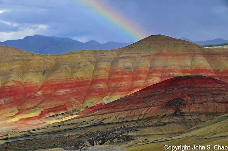 A rainbow arcs onto a peak in Painted Hills National Monument, central Oregon.