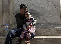 Pictured: A migrant man kisses his daughter in Victoria Square, Athens Monday 29 February 2016<br /> Re: Hundreds of migrants have been living in Victoria Square in central Athens Greece