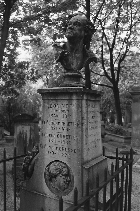 The bust of Leon Noel, French Comedien, seemingly not unaware of the ravages of time, resting atop his family grave stone at The Père Lachaise Cemetery, Paris, France