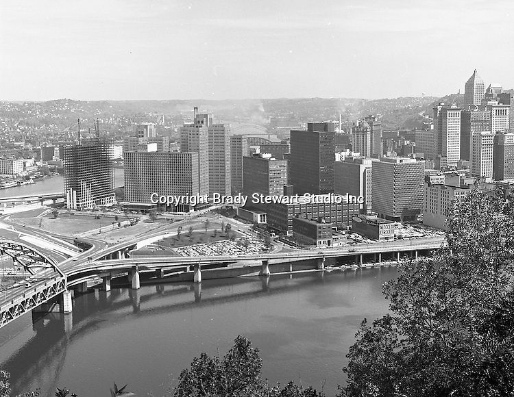 Pittsburgh PA:  View of the city from Mt Washington. The Fort Pitt Bridge in the foreground and city skyline in the background - 1964.  The Gateway Towers (left) is under construction.