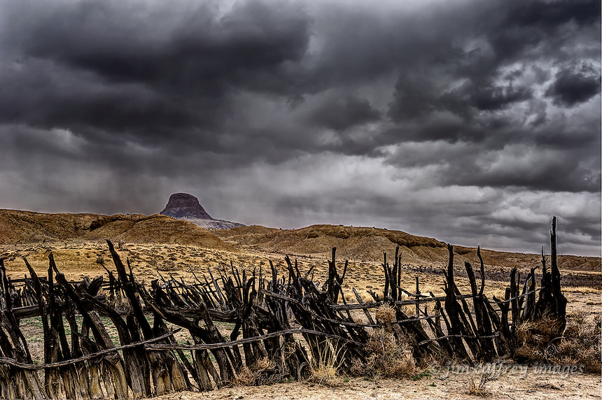 An old corral in the Rio Puerco Valley of northwestern New Mexico with Cabezon Peak in the distance under a stormy sky.