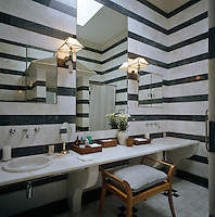 Fixtures and sconces complement the black and white marble stripe of this monochrome bathroom