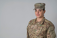 Woman in uniform studio portrait, model released,  DoD compliant for advertising, white background, framed for type