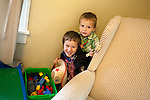 Brothers, age five, left, and age two, right, emerge from their hiding spot behind the younger boy's chair.