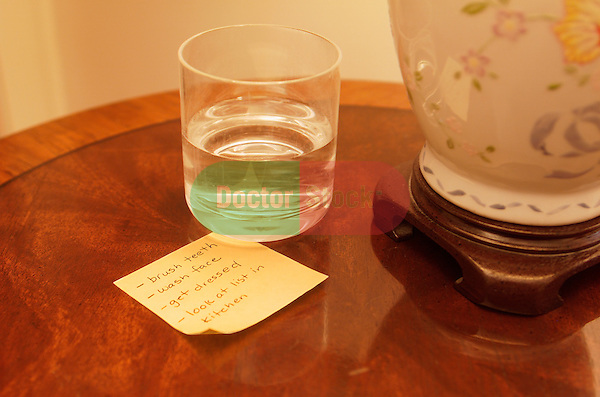 small note on nightstand to remind alzheimer's sufferer of simple tasks that might be forgotten