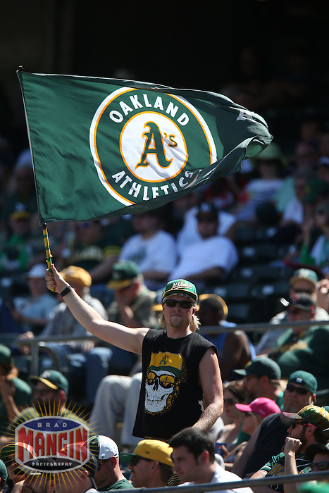 OAKLAND, CA - APRIL 30:  A fan of the Oakland Athletics waves a flag in support of his team during the game against the Los Angeles Angels at O.co Coliseum on Thursday, April 30, 2015 in Oakland, California. Photo by Brad Mangin