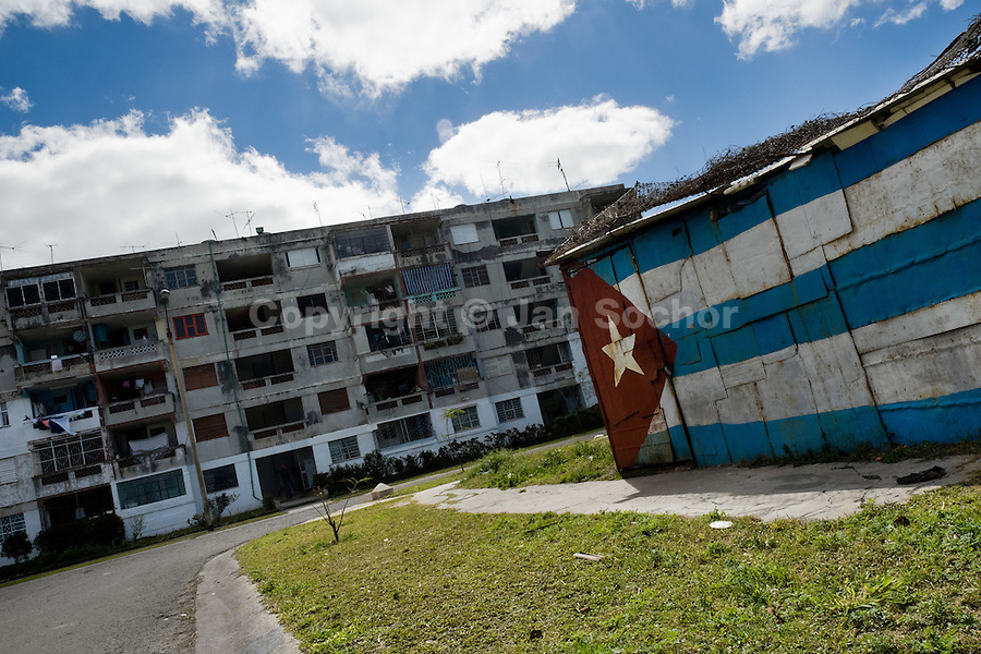 """A Cuban national flag is seen painted on a shack in Alamar, a huge public housing complex in the Eastern Havana, Cuba, 5 February 2009. The Cuban economic transformation (after the revolution in 1959) has changed the housing status in Cuba from a consumer commodity into a social right. In 1970s, to overcome the serious housing shortage, the Cuban state took over the Soviet Union concept of social housing. Using prefabricated panel factories, donated to Cuba by Soviets, huge public housing complexes have risen in the outskirts of Cuban towns. Although these mass housing settlements provided habitation to many families, they often lack infrastructure, culture, shops, services and well-maintained public spaces. Many local residents have no feeling of belonging and inspite of living on a tropical island, they claim to be """"living in Siberia""""."""
