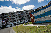 "A Cuban national flag is seen painted on a shack in Alamar, a huge public housing complex in the Eastern Havana, Cuba, 5 February 2009. The Cuban economic transformation (after the revolution in 1959) has changed the housing status in Cuba from a consumer commodity into a social right. In 1970s, to overcome the serious housing shortage, the Cuban state took over the Soviet Union concept of social housing. Using prefabricated panel factories, donated to Cuba by Soviets, huge public housing complexes have risen in the outskirts of Cuban towns. Although these mass housing settlements provided habitation to many families, they often lack infrastructure, culture, shops, services and well-maintained public spaces. Many local residents have no feeling of belonging and inspite of living on a tropical island, they claim to be ""living in Siberia""."