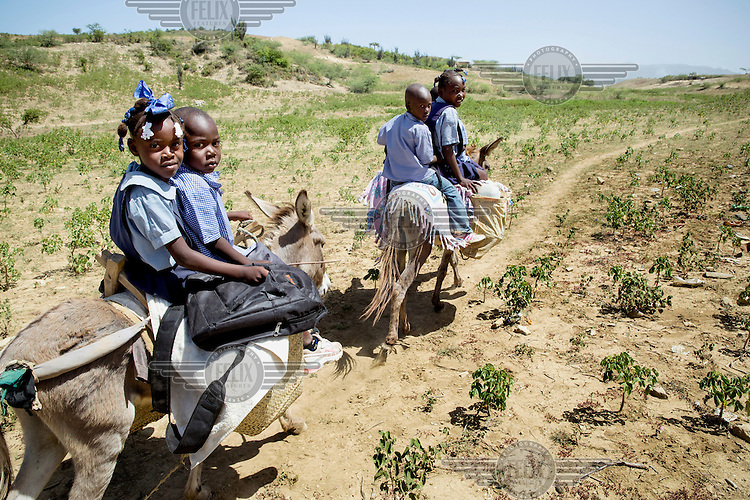 School children ride their donkeys home from school, bringing with them water from a stand pipe near their school. Mackenley, 4, and his sister Lovenica, 7, are thus in charge of their familiy's water supply.  In 2011, according to WHO and UNICEF, only 48 percent of the rural population had access to drinking water and only 29 percent had sanitation facilities. They live in the area Les Salines where there is not a single water source and say thay are happy to own a donkey because with the animal the journey is quicker and easier than walking.