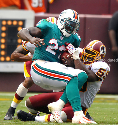 Landover, MD - September 9, 2007 -- Miami Dolphins running back Ronnie Brown (23) is tackled by Washington Redskins linebacker London Fletcher (59) and safety Sean Taylor (21) after a 5 yard gain late in the fourth quarter at FedEx Field in Landover, Maryland on Sunday, September 9, 2007.  The Redskins won the game in overtime 16 - 13..Credit: Ron Sachs / CNP