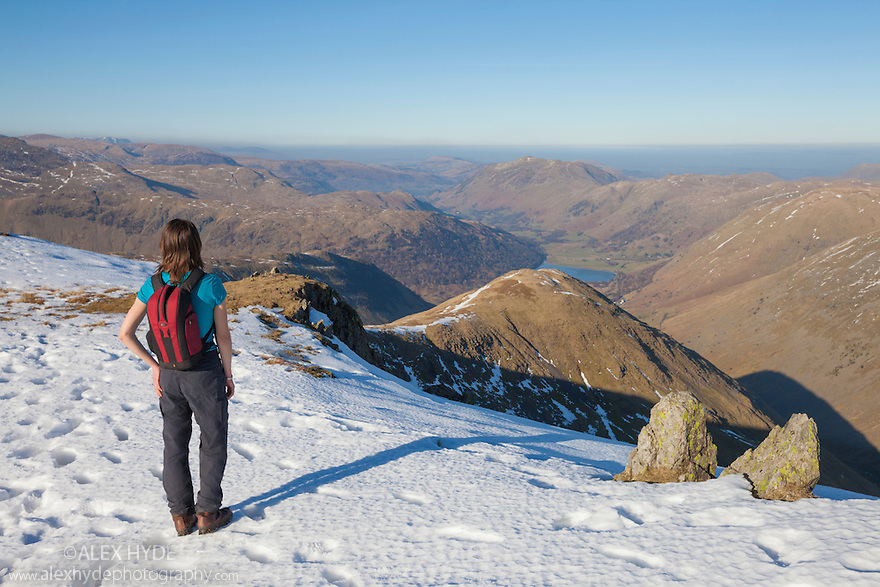Female hiker looking out from the snow-capped summit of Red Screes (776 metres). Lake District National Park, Cumbria, UK. February.