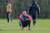 SWANSEA, WALES - JANUARY 28:  Jonjo Shelvey of Swansea City  sits and watches team mates during training  on January 28, 2015 in Swansea, Wales.