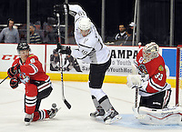 San Antonio Rampage left wing Garrett Wilson, center, attempts a deflection between Rockford IceHogs goaltender Kent Simpson, right, and Rockford defenseman Jared Nightingale during the second period of an AHL hockey game, Saturday, Oct. 5, 2013, in San Antonio. (Darren Abate/M3D14.com)