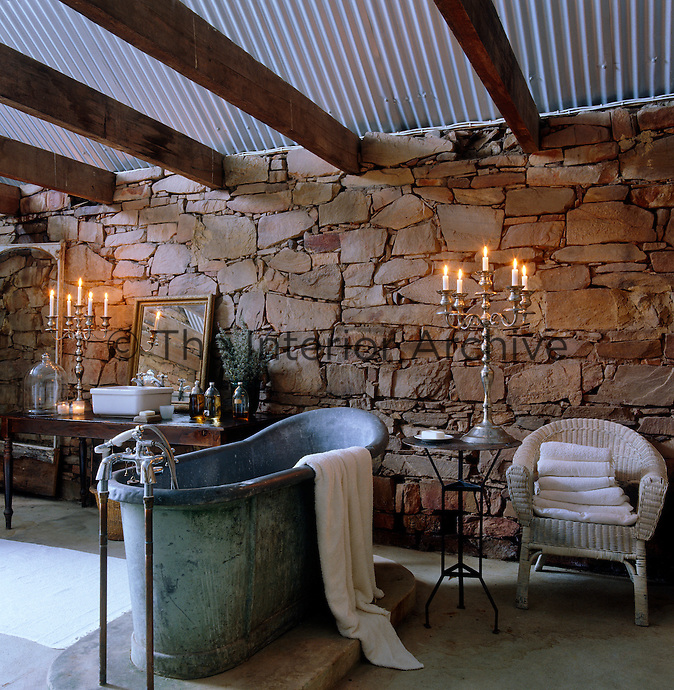 An antique lead bath tub lit by silver candelabra is placed against a wall of natural stone beneath a roof of corrugated iron