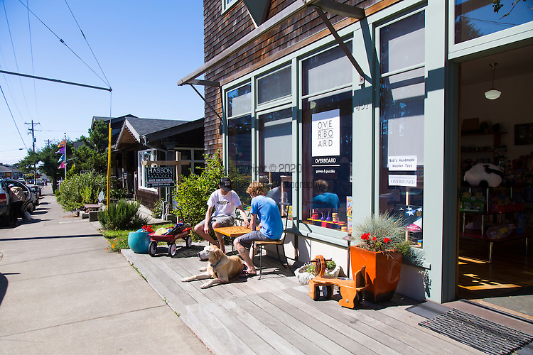 """Manzanita, Oregon, located on Neahkahnie Beach, is a small beach town located in Tillamook County on the Northern Oregon coast.  Manzanita means """"little apple"""" in Spanish. Pictured here is toy shop Overboard that specializes in hand made and unusual towns.  Two wind surfers take a break and play a game of checkers outside the shop"""